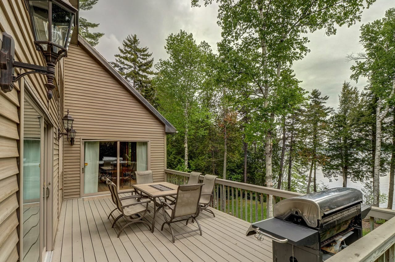 a porch with a table and a grill that overlooks the forest near moosehead lake