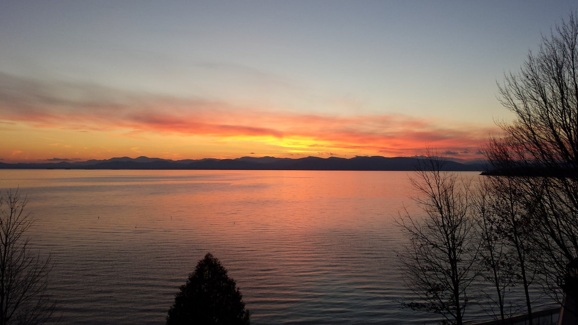 lake champlain with the sun setting over the hills in the background