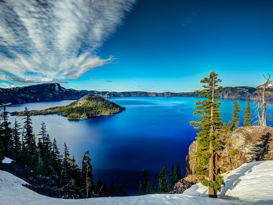 the snowy ground overlooking a view of Crater Lake, OR