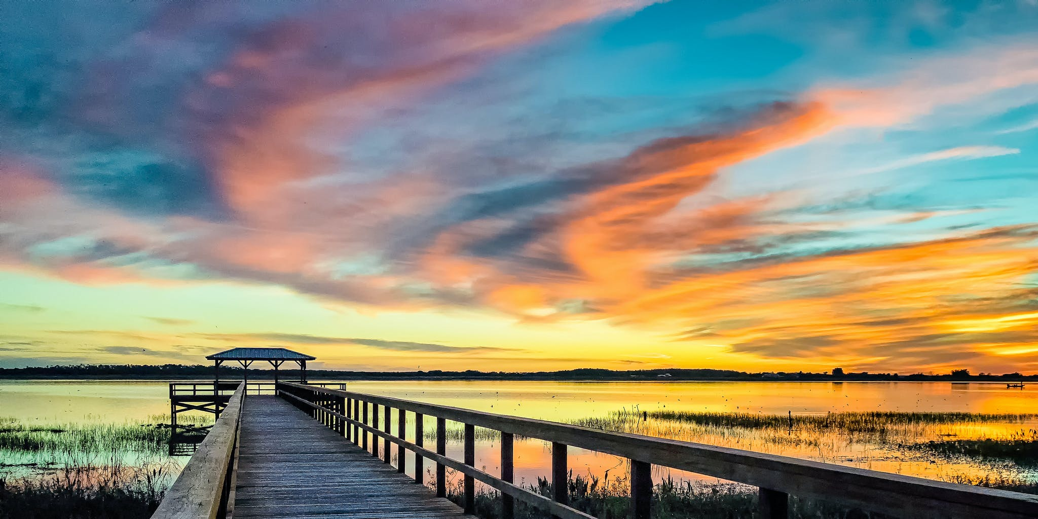 the colorful sky brightens up a dock over Lake Tohopekaliga, FL