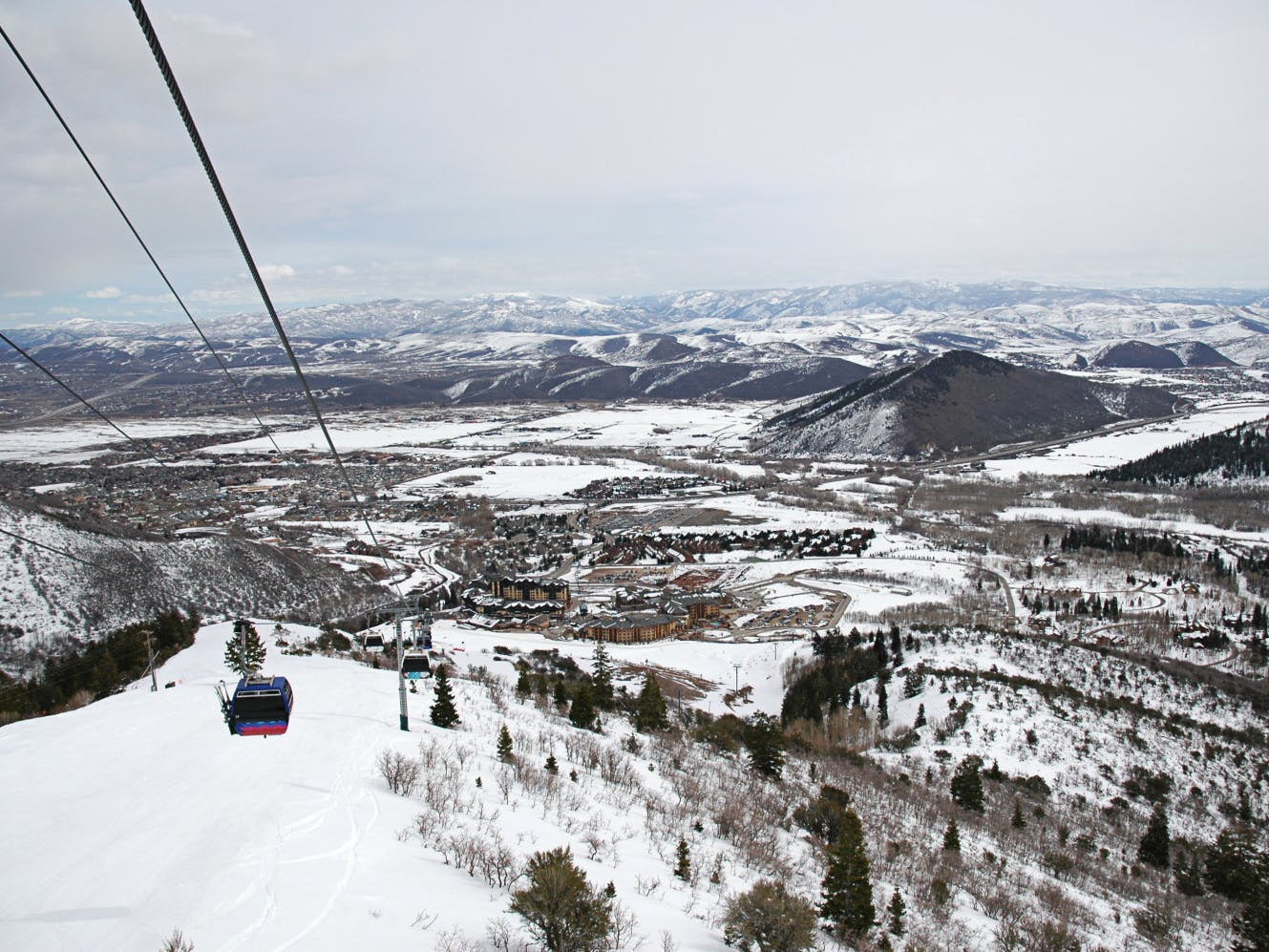 a gondola going down the mountain with a view of Park City
