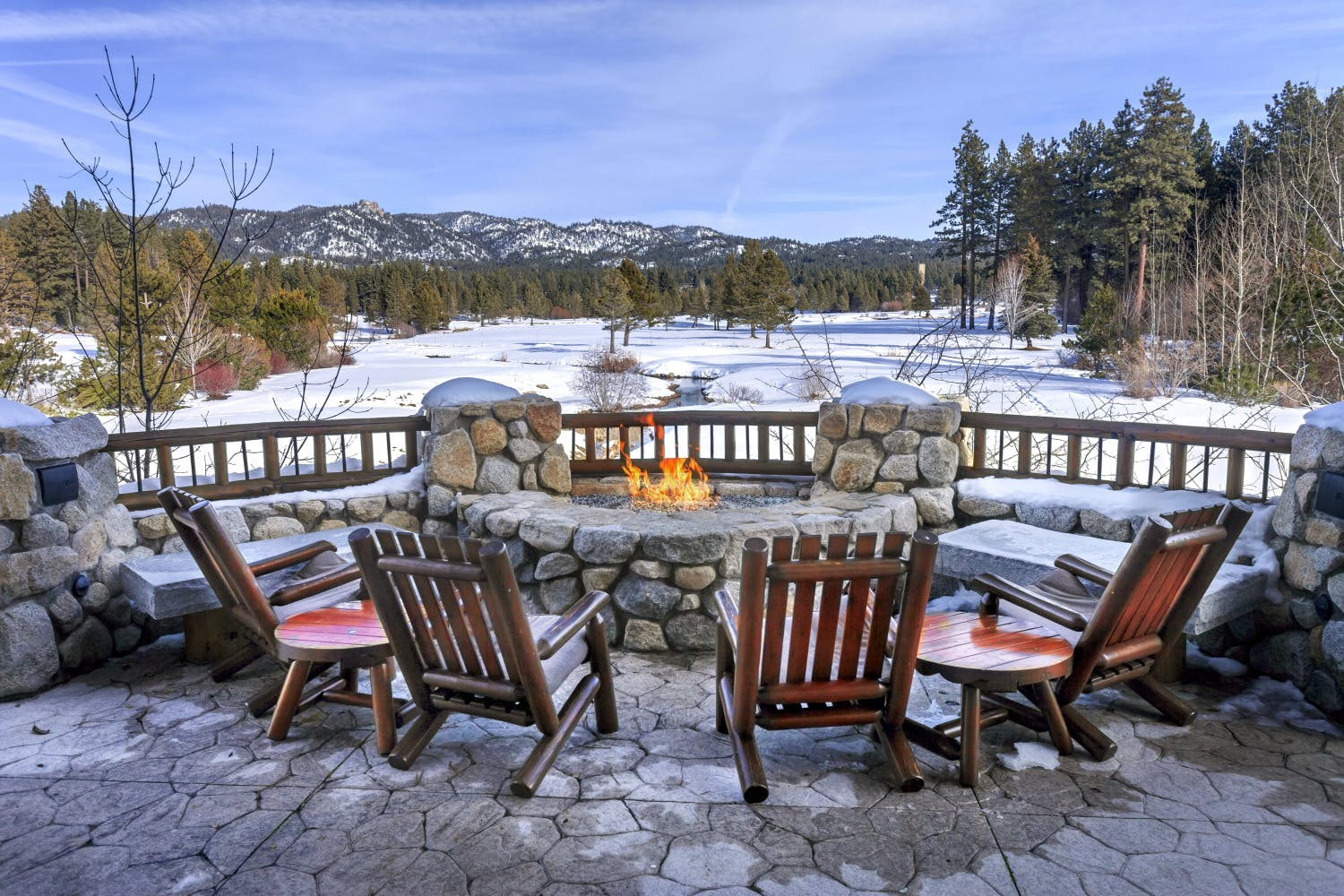 chairs placed around an outdoor fire pit with a view of the forest near Tahoe