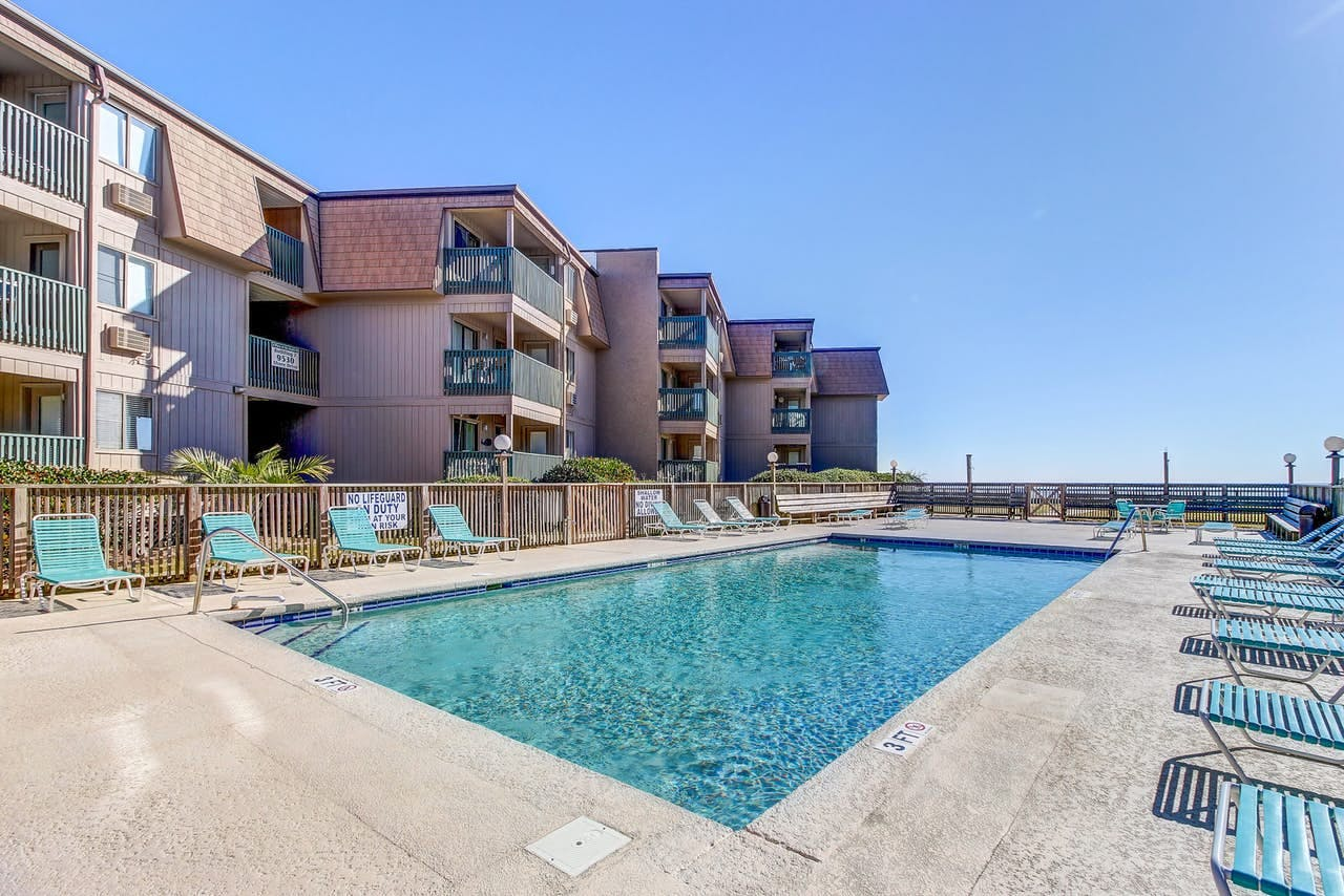Vacation condo building with outdoor pool and lounge chairs located in Myrtle Beach