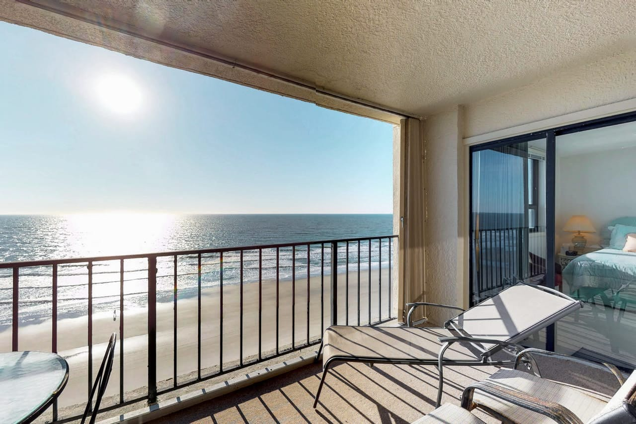 Balcony of Myrtle Beach oceanfront condo with lounge chairs and outdoor dining table
