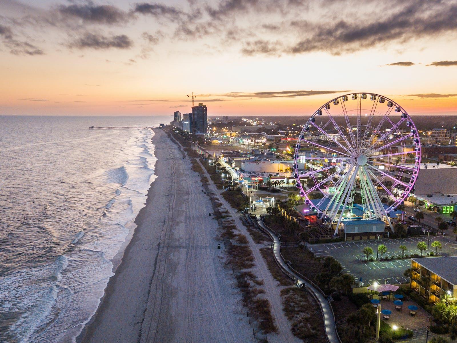 Aerial view of Myrtle Beach, SC with ocean waves, beach, boardwalk and ferris wheel