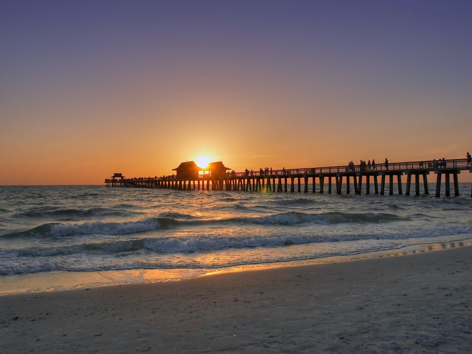 the sun setting over the ocean in Naples, Florida