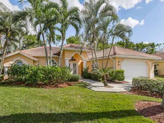 Orange vacation rental surrounded by palms located in Naples, FL