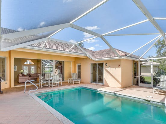 Enclosed outdoor pool and patio with lounge chairs