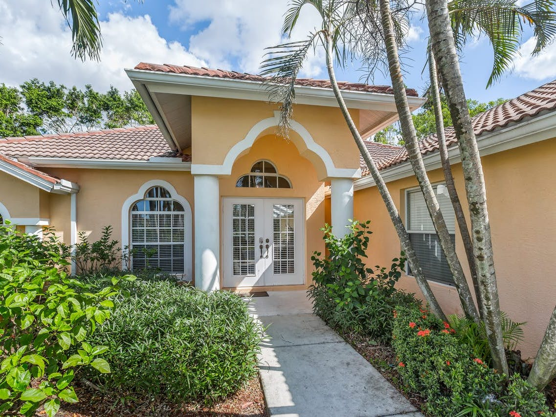Orange-hued vacation rental with terracotta roof located in Naples, FL