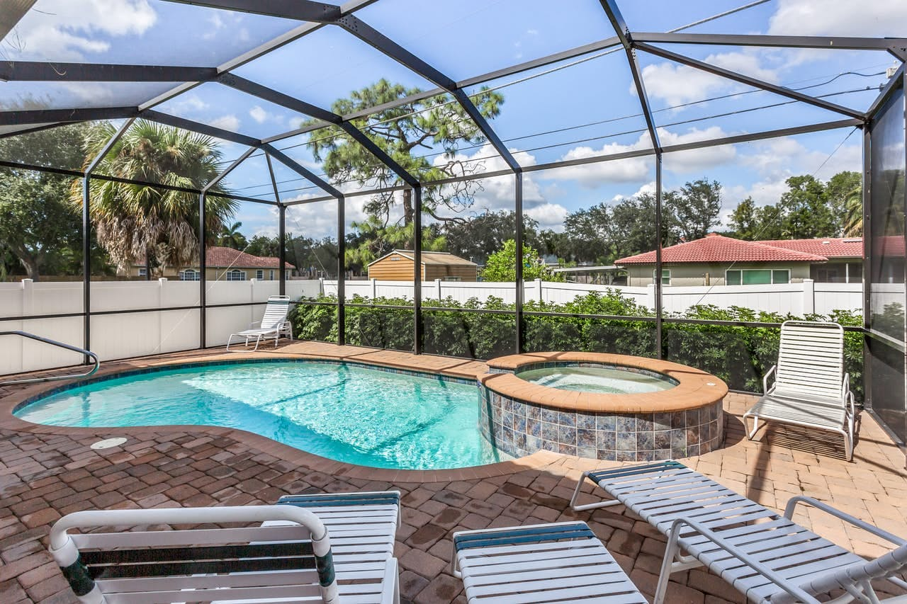 Screened-in outdoor pool and hot tub with lounge chairs