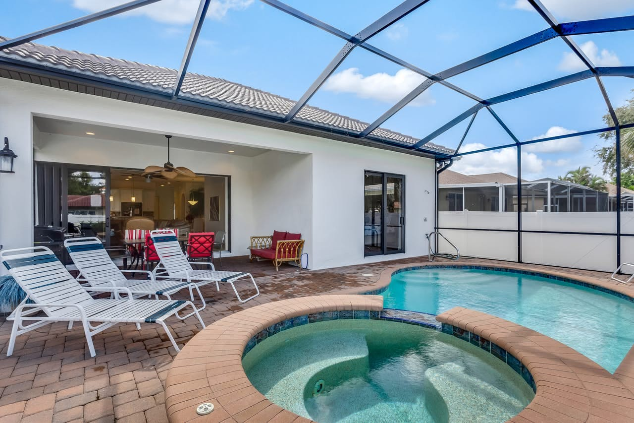 Enclosed pool with patio furniture and hot tub