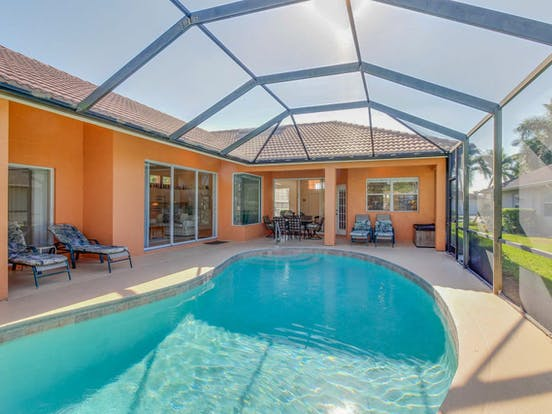 Peach-hued vacation rental with enclosed outdoor pool located in Naples, FL