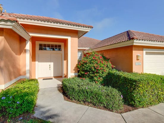 Peach-hued vacation rental entrance located in Naples, FL