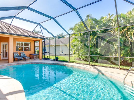 Enclosed pool of Naples, FL vacation rental surrounded by lush greenery
