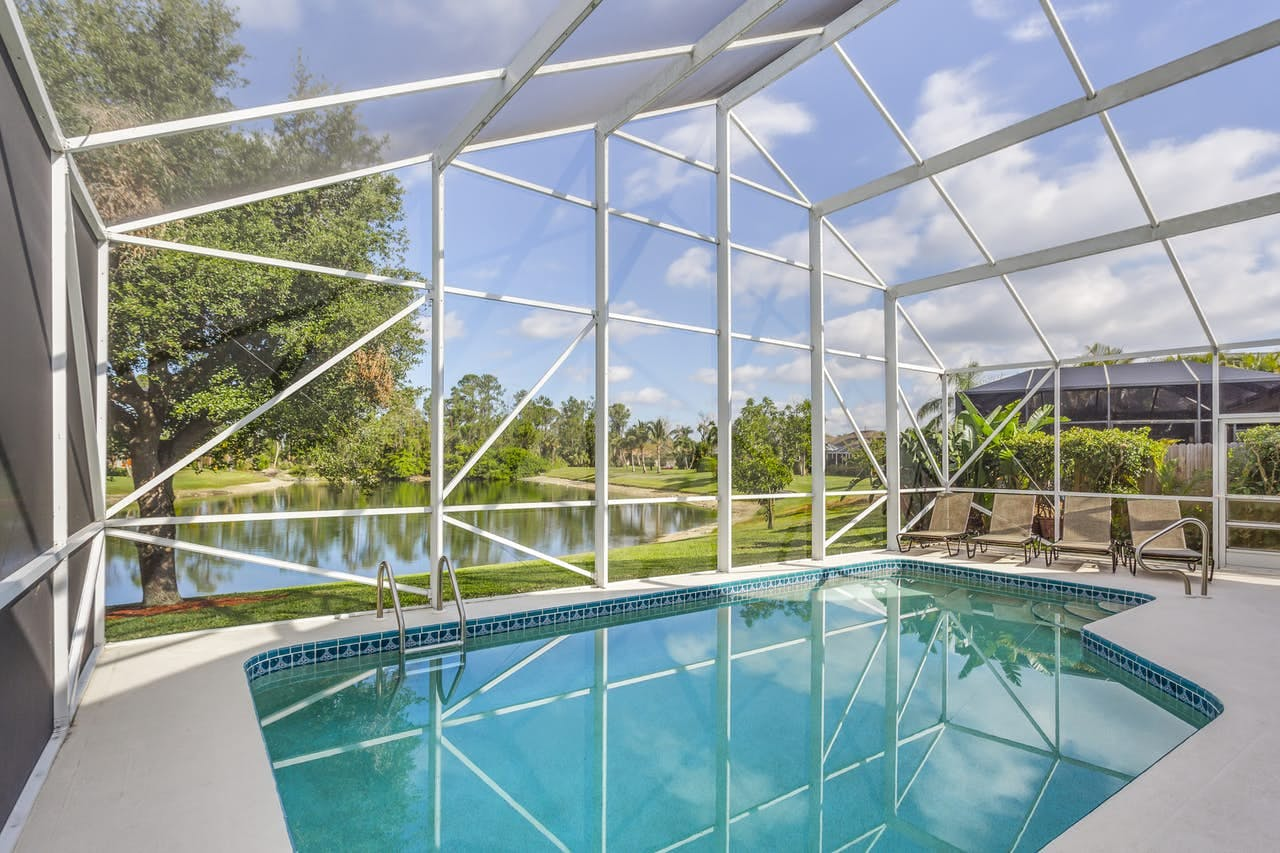 Naples, FL enclosed outdoor pool with lounge chairs and golf course views