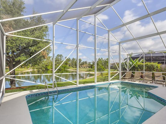 Enclosed vacation home pool in Naples, FL with views of nearby golf course