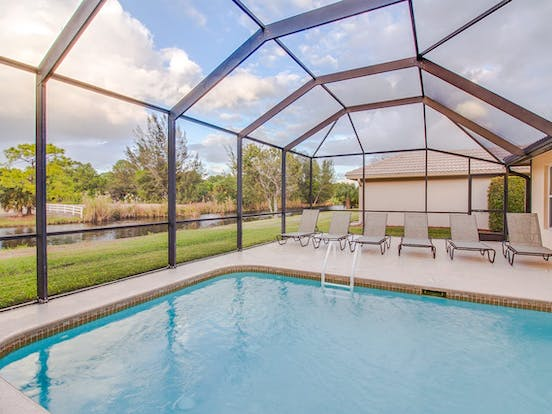 Screened back patio with outdoor pool and lounge seating with gorgeous views