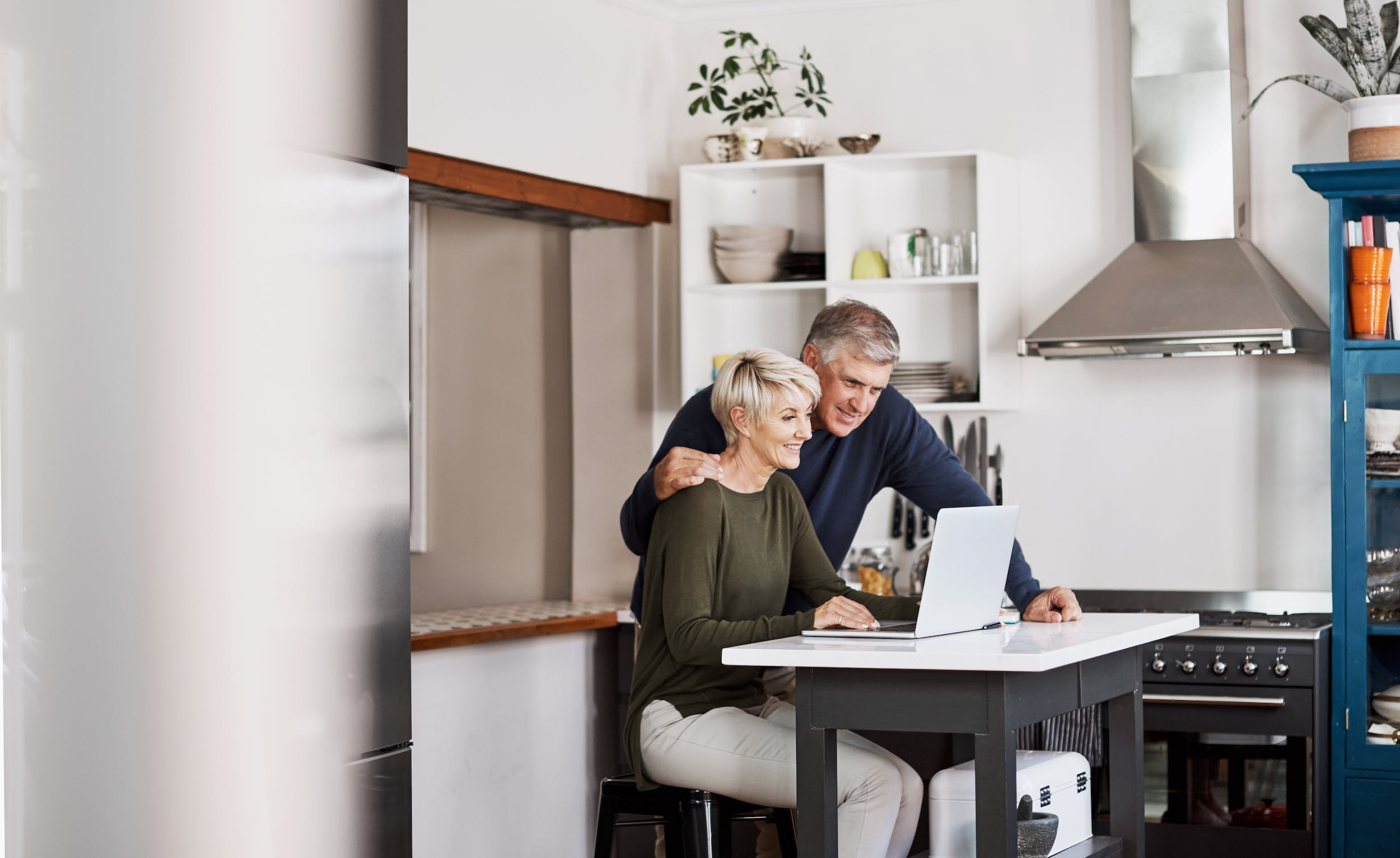 a couple at their kitchen table looking at their laptop