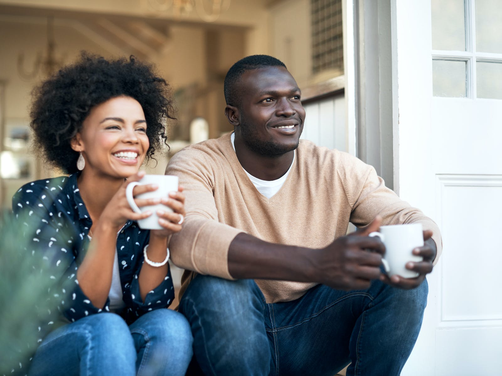 a couple enjoying coffee on their porch