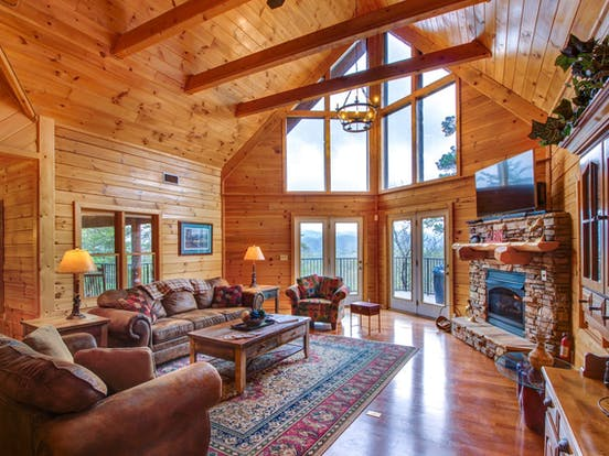 Gas fireplace, floor-to-ceiling windows and wood paneling create a cozy atmosphere at this vacation cabin