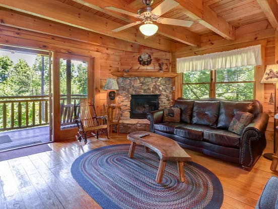 Cozy living space with fireplace and balcony at cabin in Gatlinburg, TN
