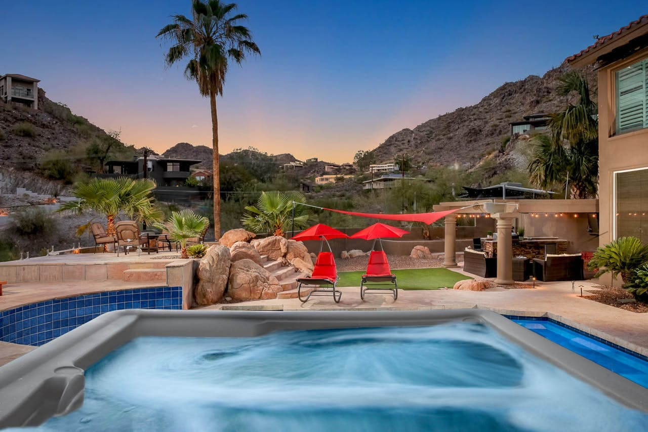 a hot tub and pool at a Phoenix vacation home with the sun setting over the hills
