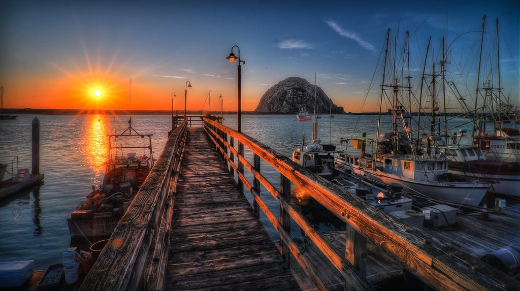 a pier going out into morro bay, with sail boats docked nearby