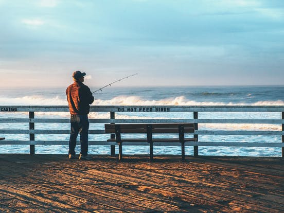 a man fishing off of the pier in pismo beach