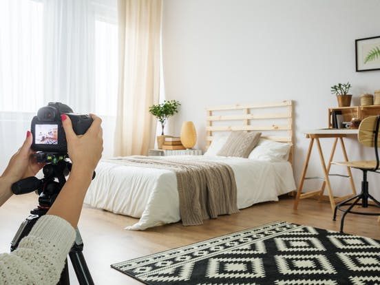 a professional photographer taking pictures of a bedroom