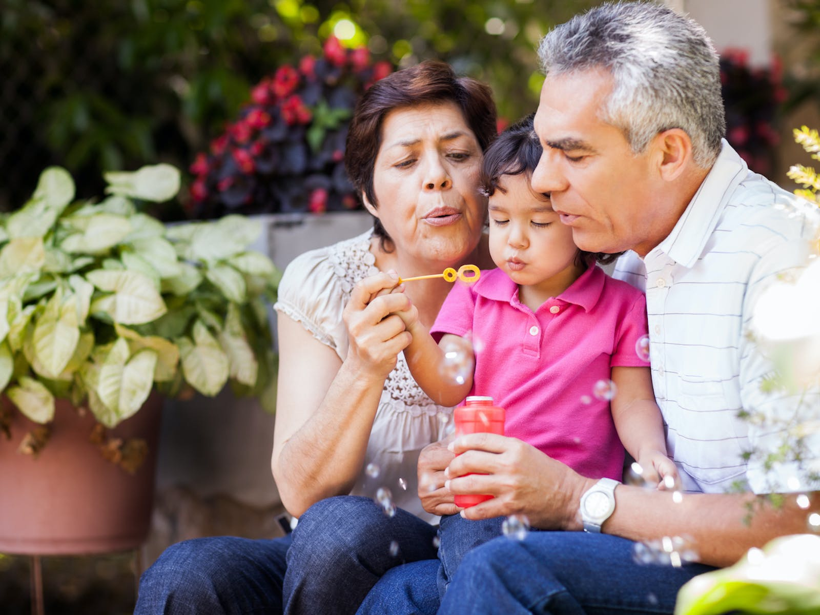 Couple blowing bubbles with young child