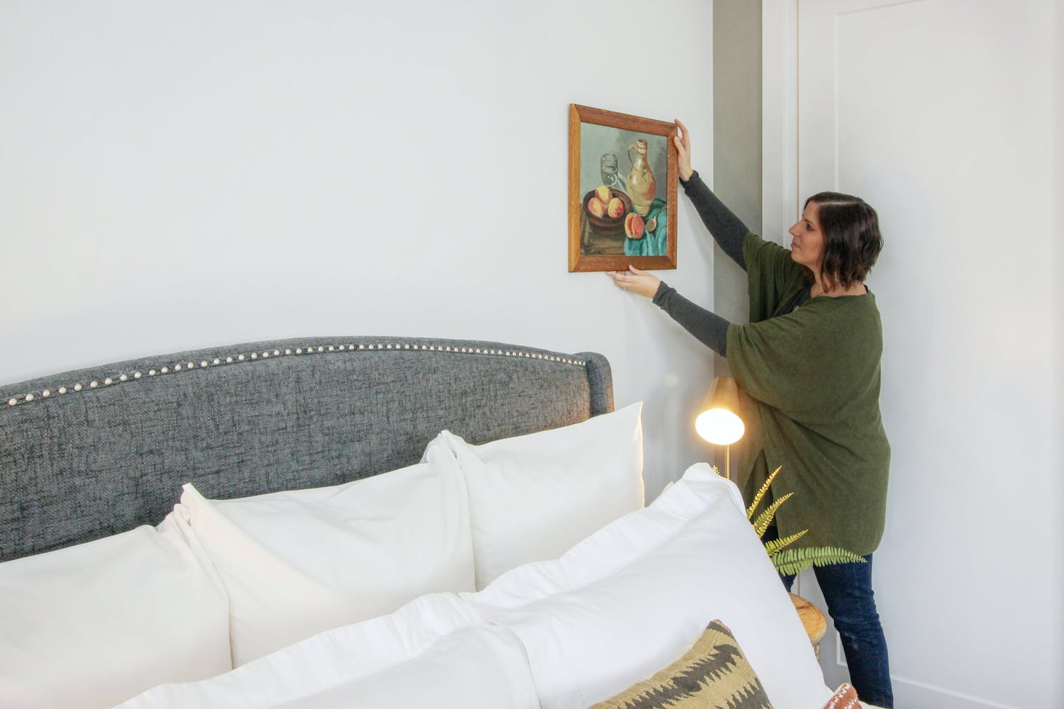 an interior decorator placing a painting on a bedroom wall