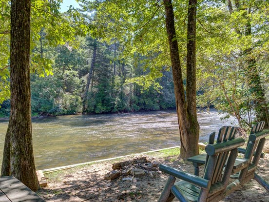 outdoor chairs overlook the Toccoa River from a riverfront vacation home