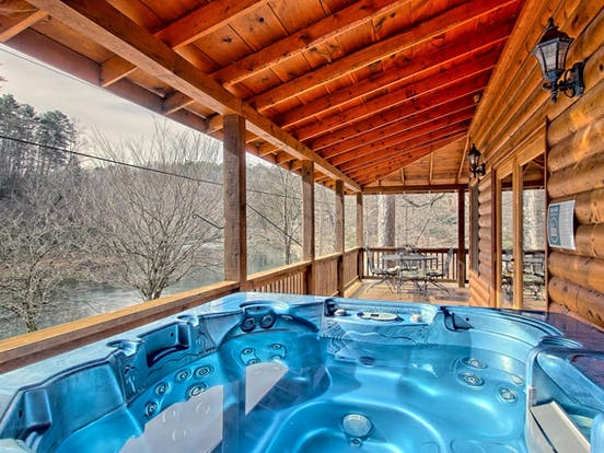 North Georgia vacation rental with deck and hot tub overlooking a river
