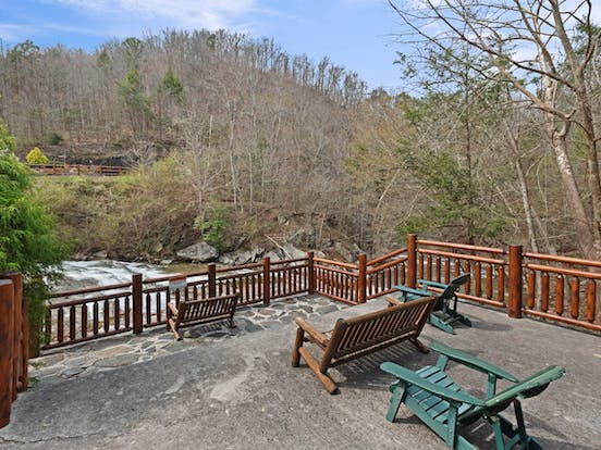Adirondack chairs sit outside a vacation rental overlooking a river in Pigeon Forge, TN