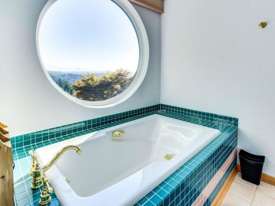 teal tiled bathtub with beautiful views of oregon