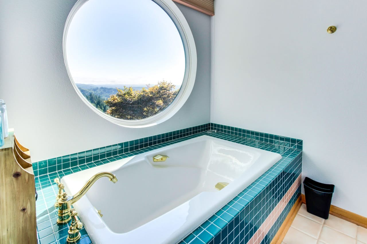 a bathtub with a round window that overlooks the forest at Forest Ridge Retreat in Coos Bay, OR