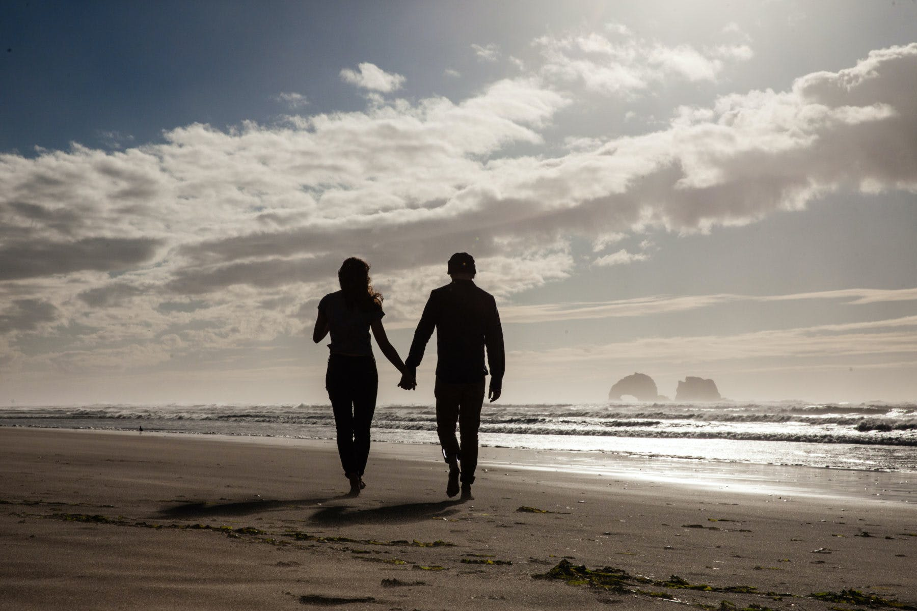 a couple holding hands walking along an oregon beach