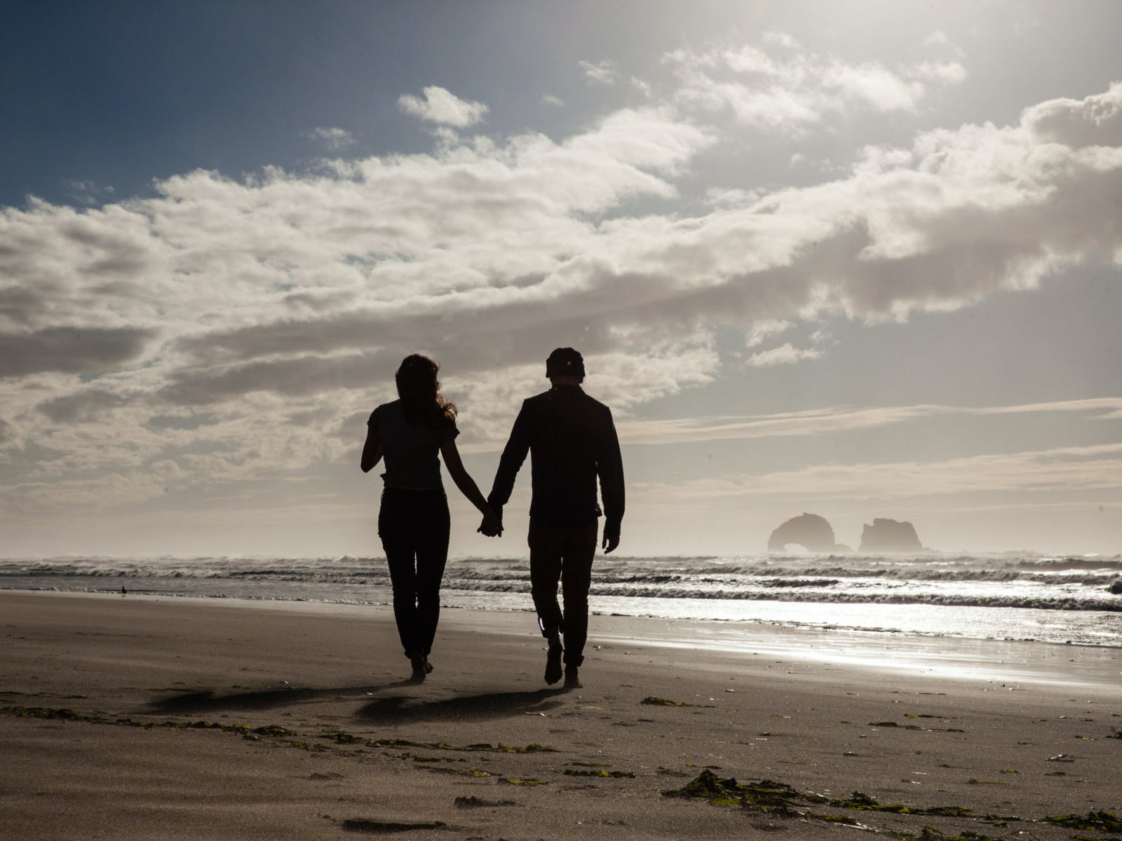 a couple holding hands walking along an oregon beach