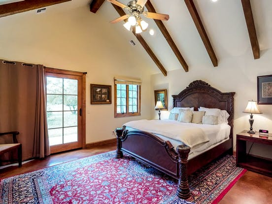 Bedroom of Fredericksburg, TX vacation rental with exposed wood beams and french doors that open to the patio