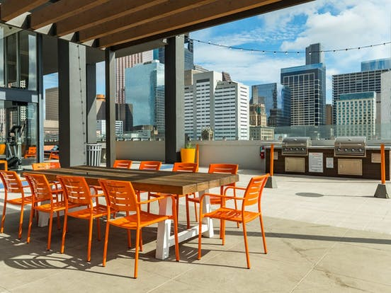 Communal rooftop area with plenty of seating, grills and great views of downtown Houston