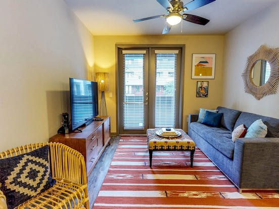 Artfully decorated living space of Dallas, TX vacation rental with large flat screen tv, beautiful area rug and patio