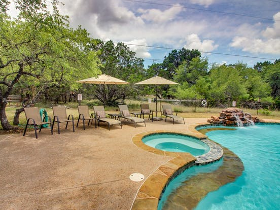 Outdoor pool and hot tub at Whitetail Ridge Retreat in Dripping Springs, TX