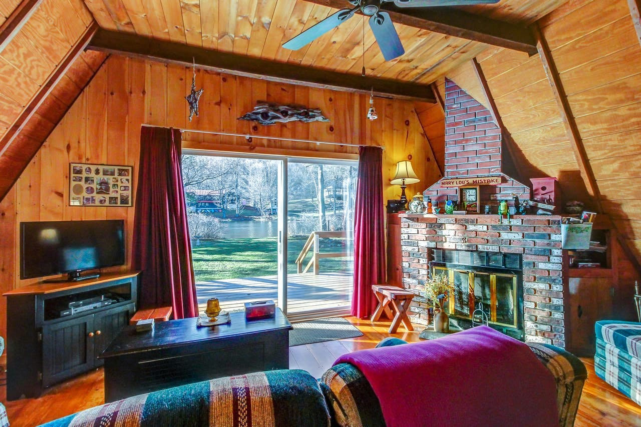 Cozy living space of A-frame cabin with fireplace and view of Lake Pauline