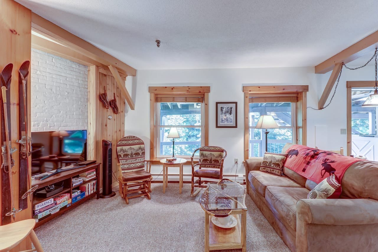Living area of vacation rental in Vermont with ski decor, board games, and amble seating
