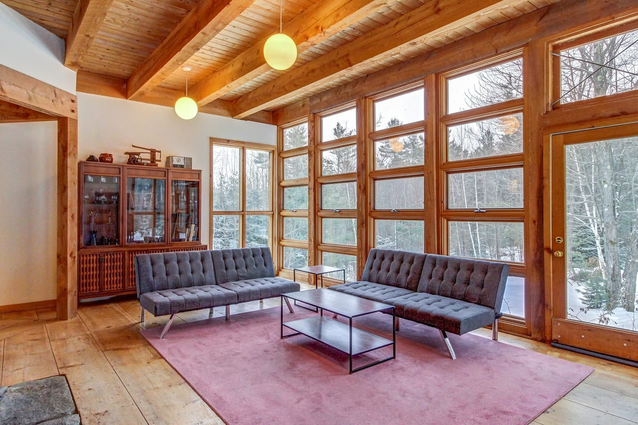 Floor-to-ceiling windows highlight the fresh snow in this Vermont vacation rental