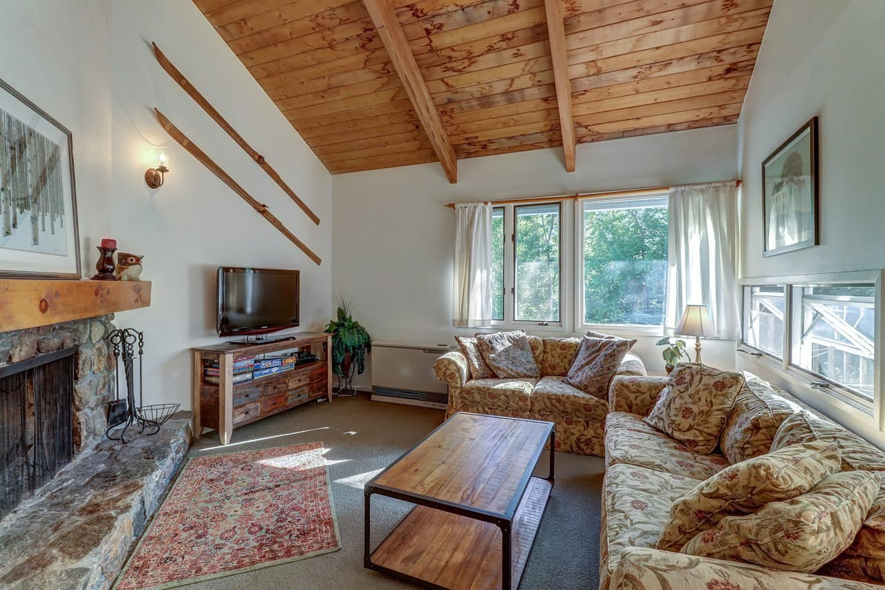 Living area with stone fireplace surrounded by cozy couches