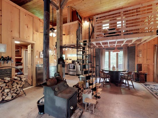 Interior of West Wardsboro, VT vacation rental with spiral staircase, wood-burning stove, kitchen and dining area