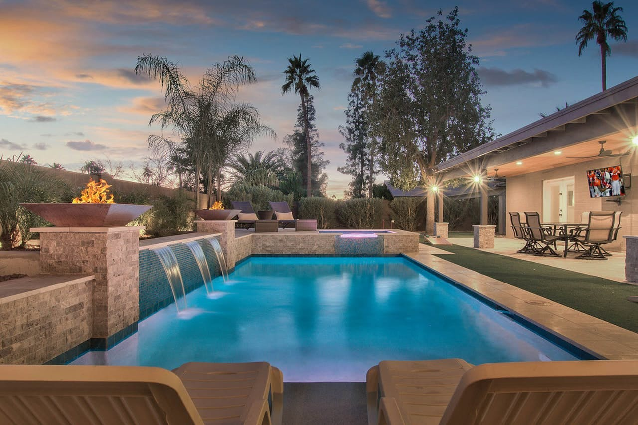 a luxury villa in phoenix with an outdoor pools with fountains flowing into the pool