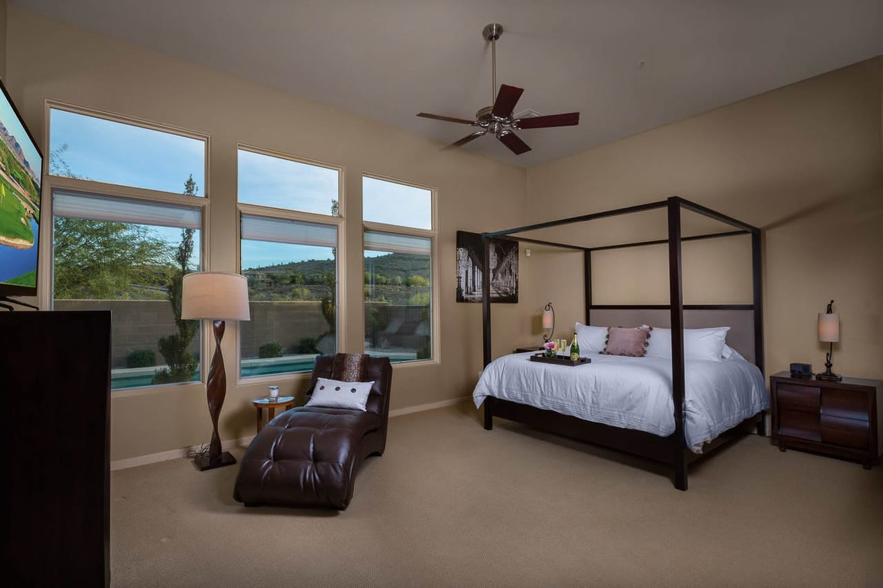 a king size bed in a luxury scottsdale home, with views on the pool in the backyard