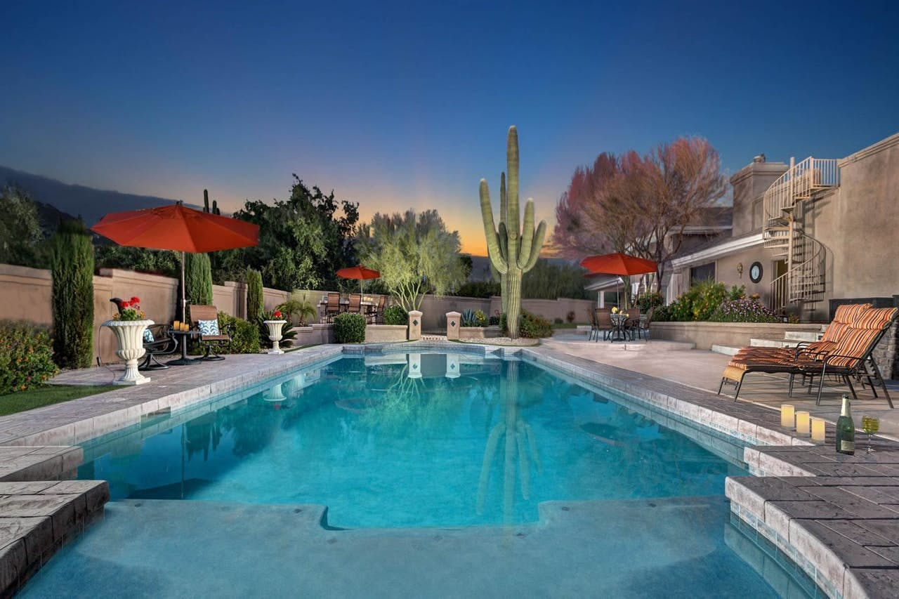 a large private swimming pool with a cactus in the background in scottsdale, AZ